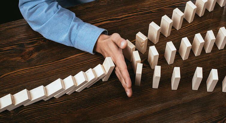 Dominoeffekt - hånd stopper dominobrikker. Foto: Colourbox